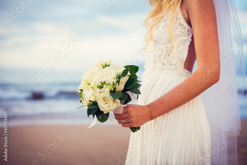 Fotografie, Obraz  beautiful bride standing by the beach at sunset