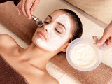 Spa therapy for woman receiving facial mask