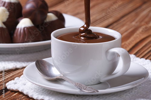 Foto op Canvas Chocolade Chocolate is poured into a cup closeup on background sweets