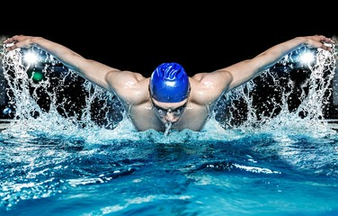 Fototapeta Muscular young man in blue cap in swimming pool