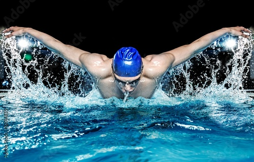 Fotografía  Muscular young man in blue cap in swimming pool