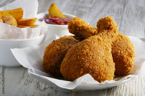 breaded chicken legs with fried potatoes