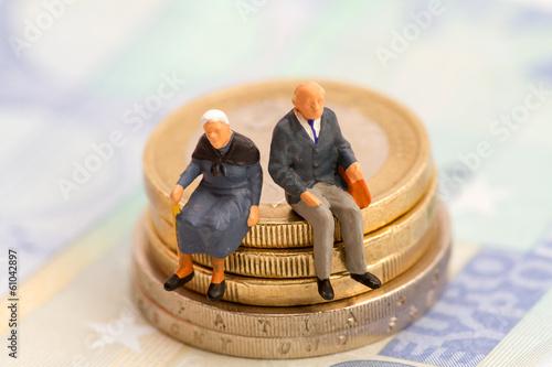 Fotografía  Senioren sitzen auf Muenzstapel