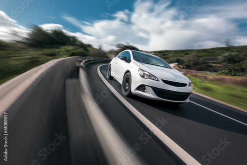 Fototapeta White car cornering in mountain road with speed blur obraz