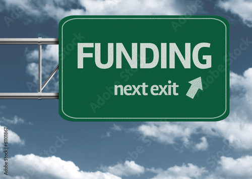 Fotografía  Funding, next exit creative road sign and clouds