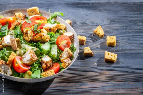 Fotografía  Healthy Caesar salad made of fresh vegetables on blue table