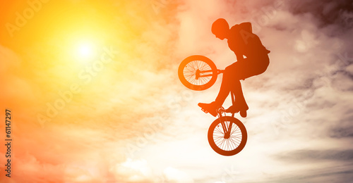 Man doing an jump with a bmx bike against sunshine sky. Wallpaper Mural