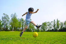 Young Asian Boy Playing Soccer...