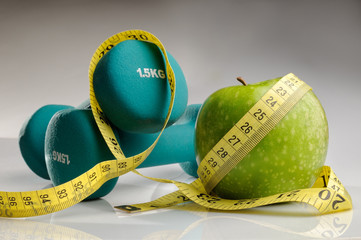 healthy apple, measuring tape and dumbbells