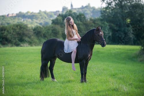Girl sitting bareback on her pony Canvas Print