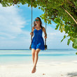 Woman in blue dress swinging at beach