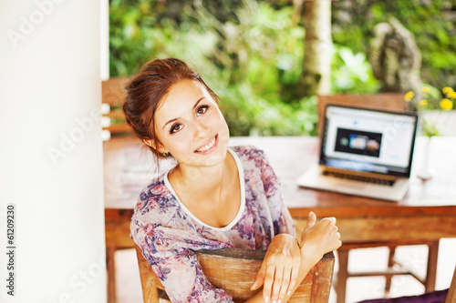 Young woman at home with laptop Poster
