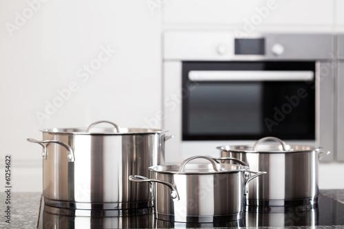 Fotografie, Obraz  Three metal pots on induction hob