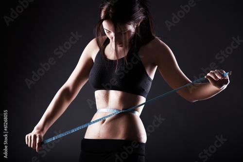 Fotografia  Fitness woman measuring her waist, weight loss