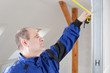 Young man/tradesman/craftsman measure with metre/meter