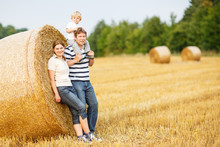 Happy Family Of Three On Yellow Hay Field In Summer.