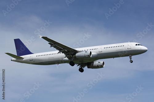 bialy-samolot-z-blekitnym-ogonu-ladowaniem-w-slonecznym-dniu