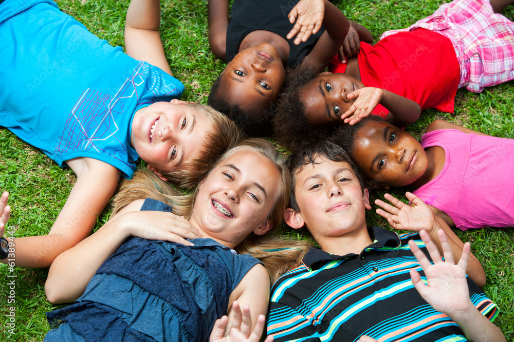 Fototapeta Diverse group og children laying together on grass.