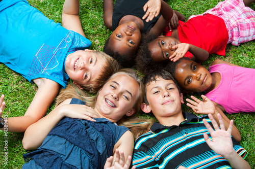 Photo  Diverse group og children laying together on grass.