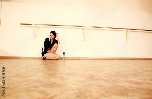 Tired young fit woman leaning on the wall at gym Canvas Print