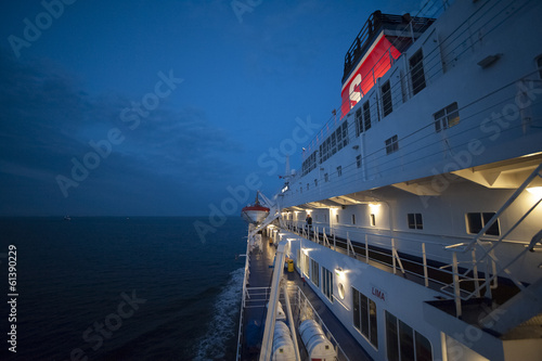 Fotografía  Fragment of a ferry in the sea at night, with illuminated decks