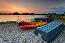 A Bunch Of Kayaks And Boat Stranded With A Sunset View.