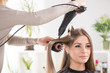 Hairdresser drying long hair with hair dryer and round brush.