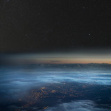 The Earth at night. City lights below the clouds, stars above.