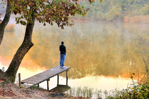 Fotografía  autumn landscape reflected in the water facing the young
