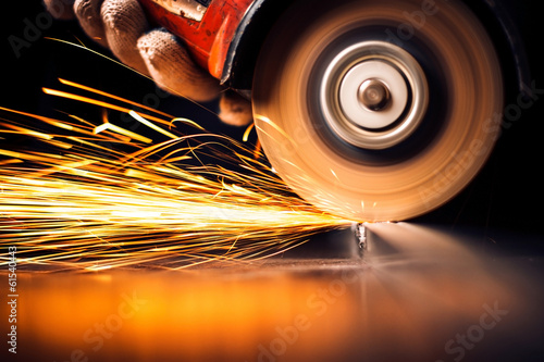 Fotografie, Obraz  Worker cutting metal with grinder. Sparks while grinding iron
