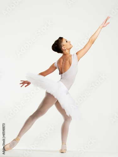 Fotografie, Obraz  Young ballerina dancer in tutu showing her techniques