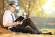 Young male sitting on green grass and reading book in park