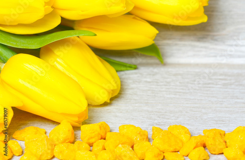 Gelber Tulpenstrauß und Dekosteine auf hellem Holz