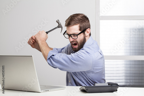 Valokuva  Furious businessman destroying his laptop with a hammer..