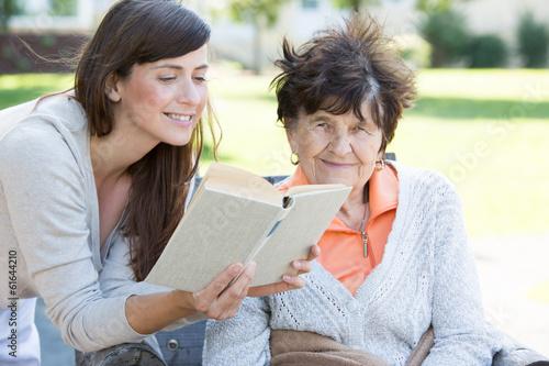Junge Frau ließt Seniorin ein Buch vor