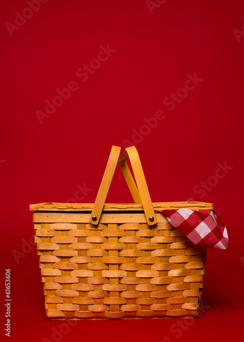 Aluminium Prints Picnic A wicker picnic basket with red gingham tablecloth on a red back