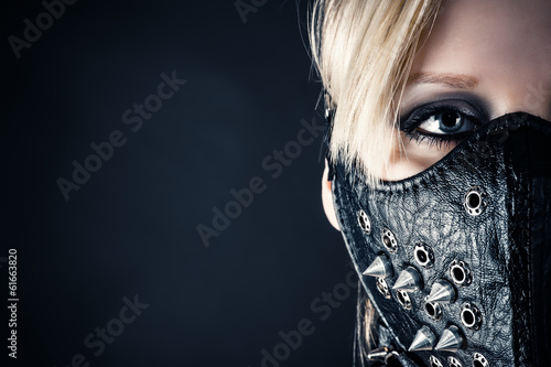 Photo  portrait of a woman slave in a mask with spikes