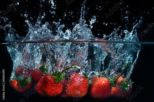 Printed kitchen splashbacks Splashing water fresh strawberry dropped into water with splash on black backgro