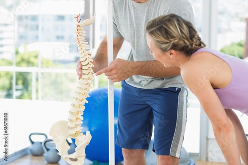 Fotografía  Trainer showing model of spinal cord to woman