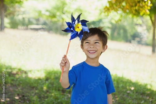 Fotografia, Obraz  Happy cute little boy holding pinwheel at park