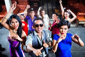 Asian people partying on dance floor in nightclub