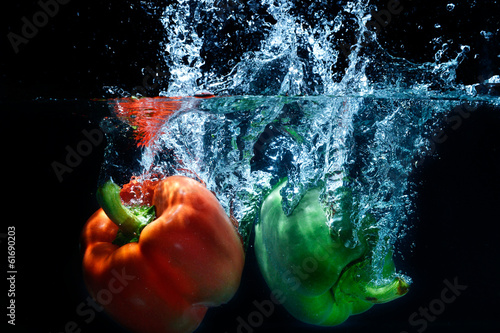 Foto op Canvas Opspattend water sweet pepper drop into water on black background.