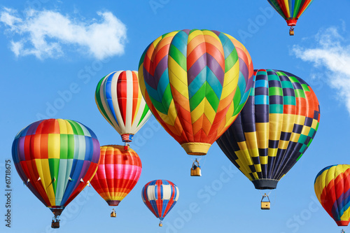 Colorful hot air balloons on blue sky with clouds