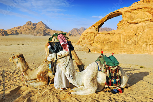 Valokuva  Bedouin man and his camels in the desert of Wadi Rum