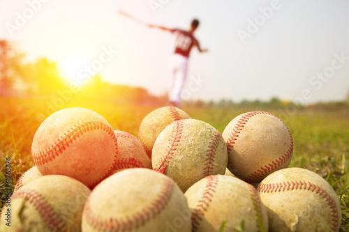 Fotografiet  Baseball players practice wave a bat in a field
