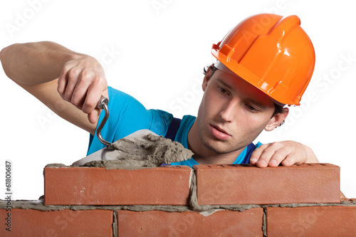 Fotografía  Concentrated bricklayer putting