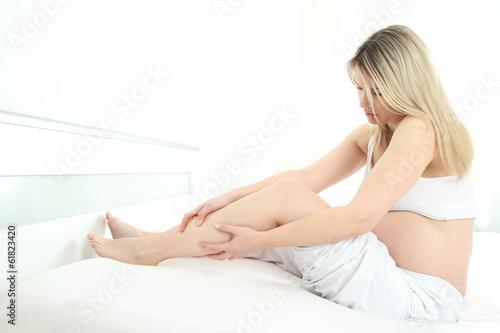 Photo  Schwangere Frau haelt ihr Beim mit Wadenkrampf