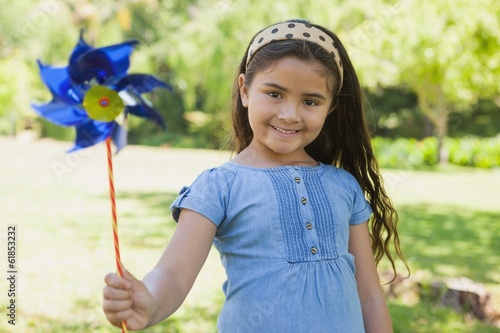 Fotografia, Obraz  Cute little girl holding pinwheel at park