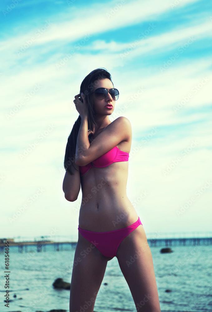 Fototapeta Sexy brunette on vacation wearing sunglasses
