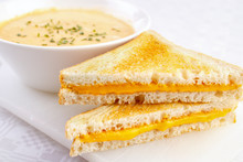 Two Cheese Sandwiches With A Bowl Of Soup